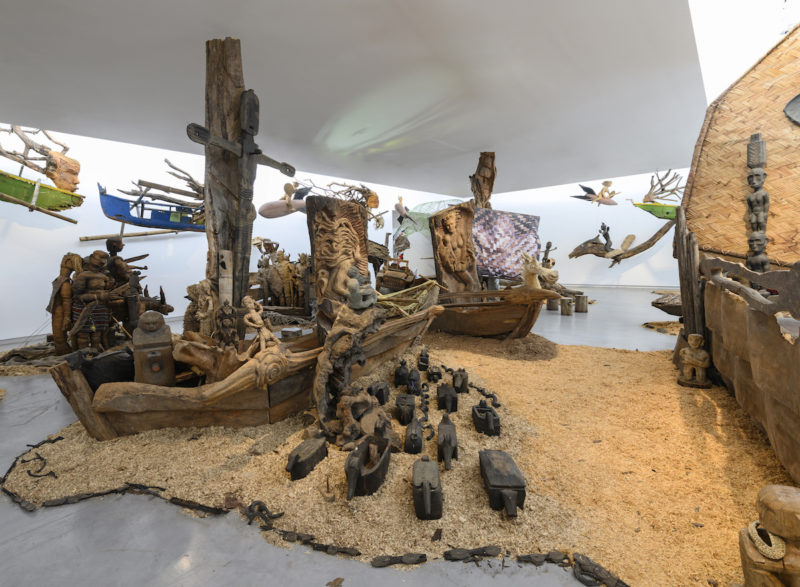 Kidlat Tahimik, Ang Ma-bagyong Sabungan ng 2 Bathala ng Hangin, A Stormy Clash Between 2 Goddesses of the Winds (WW III – the Protracted Kultur War), 2019. Wooden carved icons, ritual objects, interwoven C-print photographs, projected images, audio, mosaic, rattanbasket figurines, back-strap bamboo loom, wrought-iron launch-pads, fibreglass, root sculptures, rotten fishing boats, sawdust, bamboo fences and runo-reed fauna, dimensions variable. Installation view: Sharjah Biennial 14, 2019. Commissioned by Sharjah Art Foundation. Image courtesy of Sharjah Art Foundation