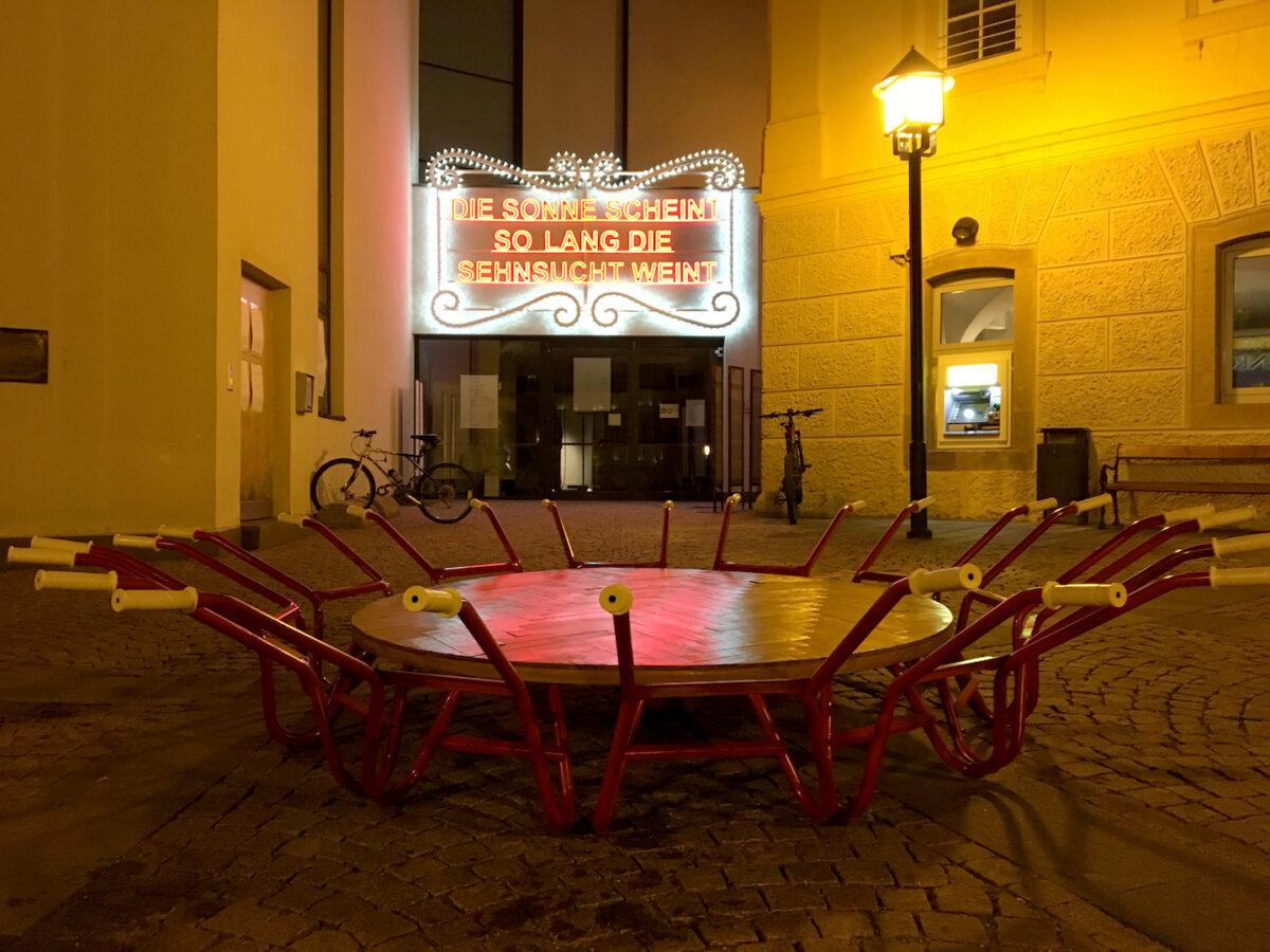 Lichtarbeit von Marnella Senatore auf der Fassade des Trenker Saals; davor Ingrid Hora, Palindrome. Biennale Gherdëina 7 2020 . Foto Erwin K. Bauer